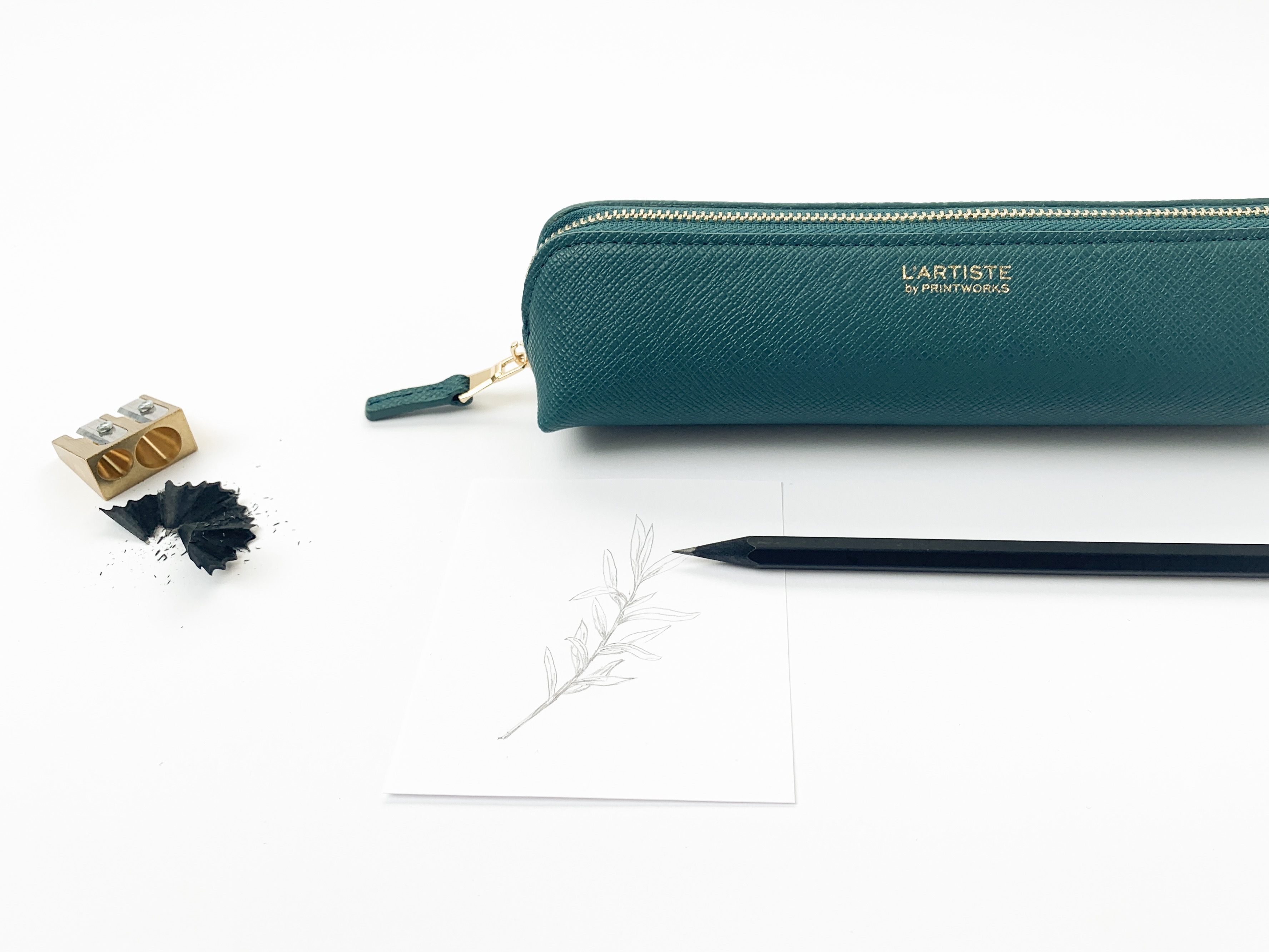 Lifestyle product photo showing a teal colored pencil case styled with a black pencil. a pencil drawing of a branch, a golden pencil sharpener and pencil shavings.