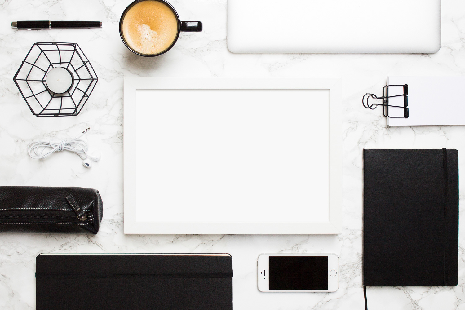 Flatlay of office items in black and white such as notebooks, a fountain pen, a Macbook, and a pencil case surrounding a white frame - by The Product Stylist