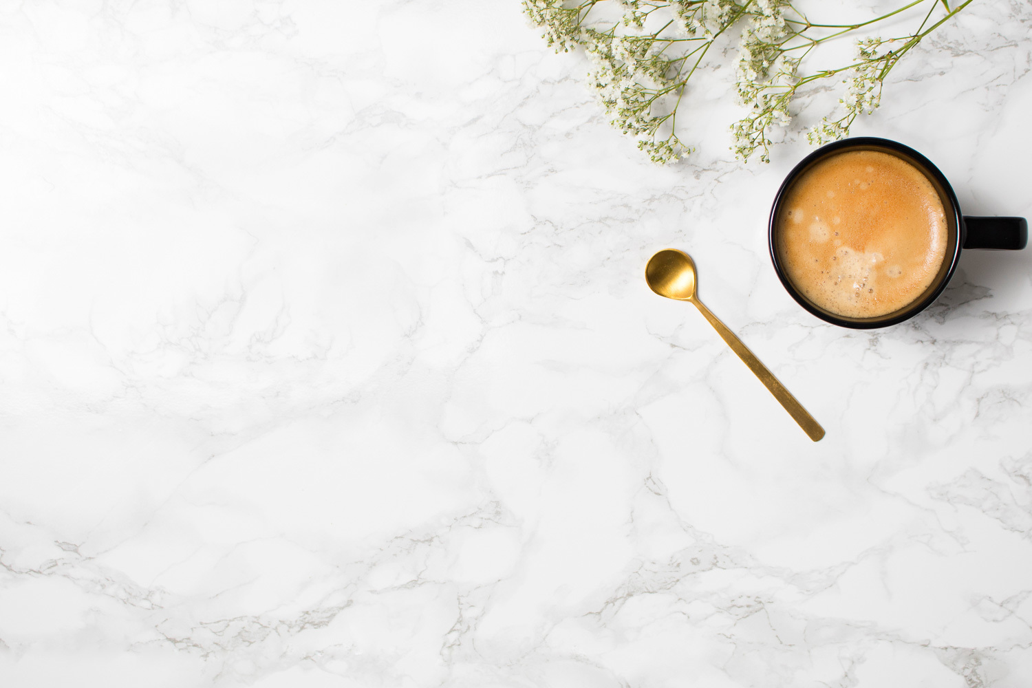 Top view of a black coffee mug, a golden spoon and baby's breath flowers on a white marble background - by The Product Stylist